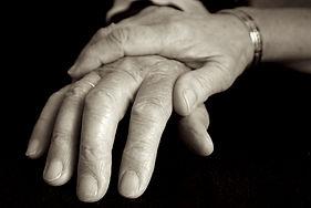 elderly spouse holding hands
