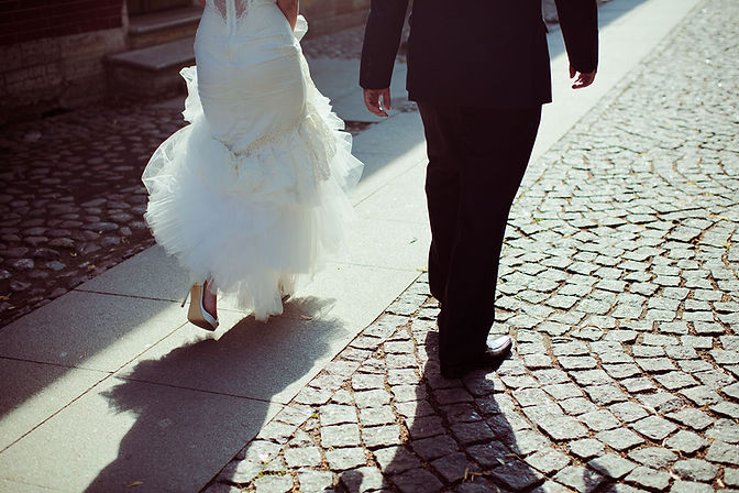 Bride in Wedding dress and Groom in Tux Walking down a brick path