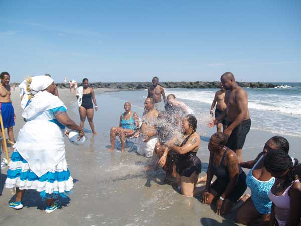 Papa Agwe giving spiritual bath on beach