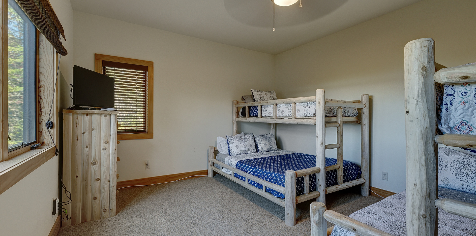 """The lower-level bunk room is a favorite with the kids! It features two sets of bunk beds, each with a twin on top and queen bed on the bottom. All beds have memory foam mattresses. The room also has a 32"""" HD television with BlueRay player and DirecTV."""