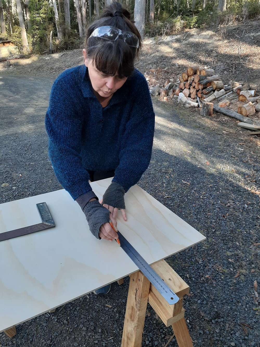 Woman marking out plywood sheet to build a seed storage box