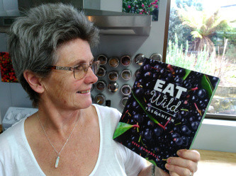 Rees Campbell holding a copy of her book, Eat Wild Tasmanian.