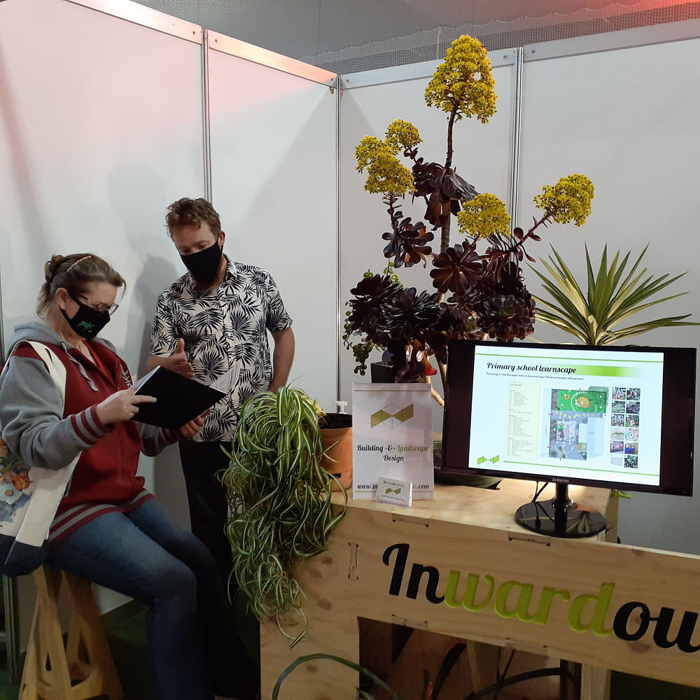 A man shows a portfolio containing building and landscape designs to a woman at a sustainable living event
