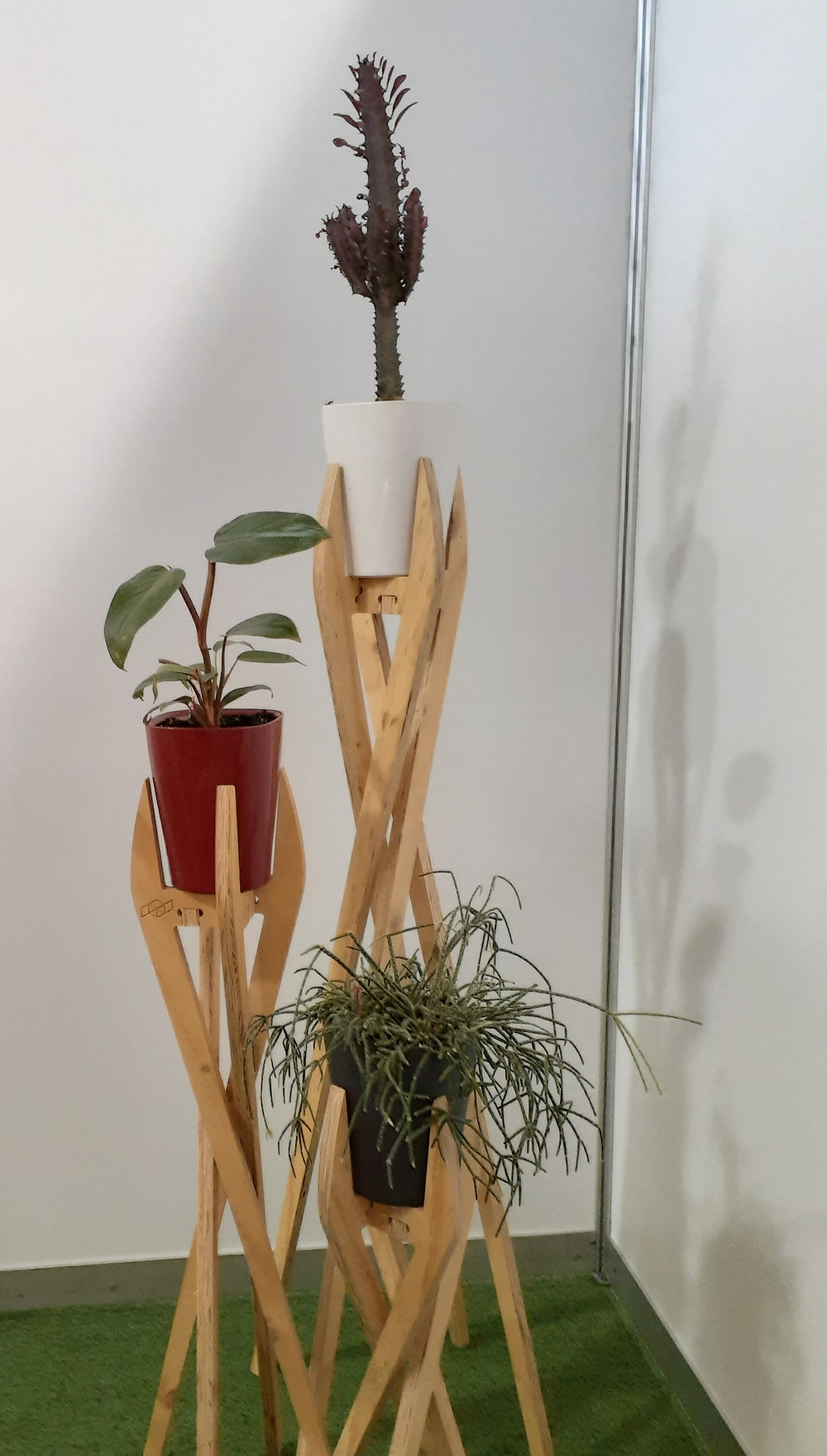 Three indoor plants on display in plant stands made from CNC cut plywood at a sustainable living event