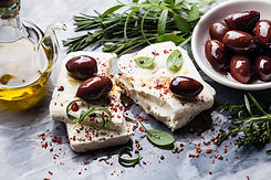 Feta cheese with olives and green herbs on gray marble background.jpg