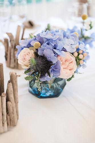 Bouquet de centre table bleu et pêche avec des photophores en bois flotté