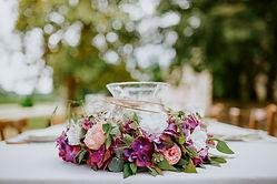 Composition florale en couronne de fleurs roses et violettes avec un photophore central