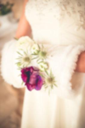 Création unique de Sylvie Borderie d'un bouquet de mariée de forme manchon décoré de dentelle et fleurs pour un mariage original en hiver