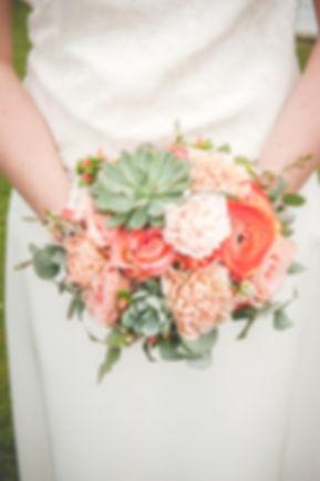 Bouquet de mariée rond dans les teintes corail et saumon avec des plantes grasses vert grisé