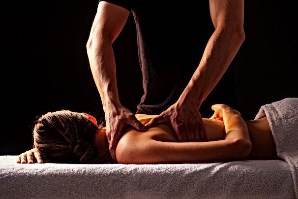 Masseur hands doing back massage to clie