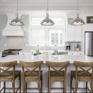 This kitchen features warm wood tones, light cabinets and tops, and plenty of natural light with wide kitchen windows and transom window above.