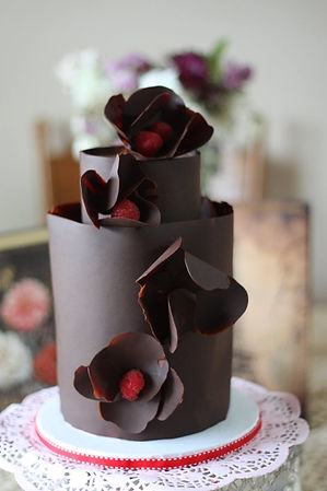Two tier chocolate covered cakes adorned with chocolate flowers