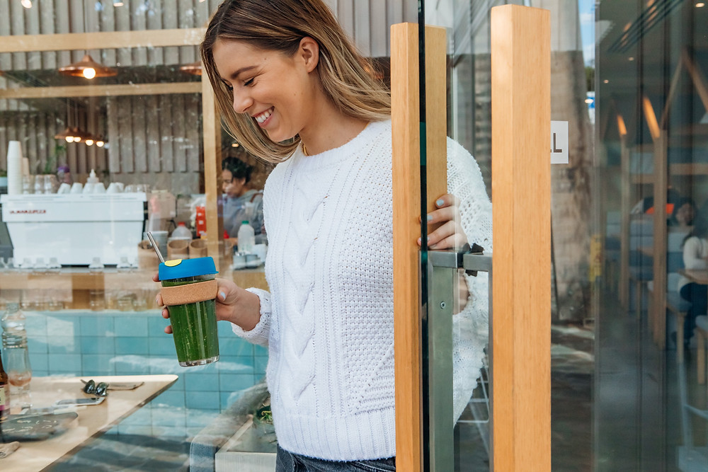 A woman exits a cafe holding a reusable cup with a metal straw.