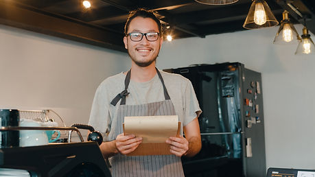 Portrait young Asian guy barista take receive order with menu feeling happy at urban cafe.