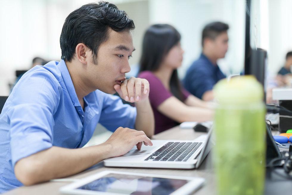 Asian Businessman Sitting At Desk Workin