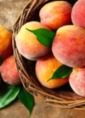 stock-photo-ripe-peaches-in-basket-on-wooden-background-297863489_edited.jpg