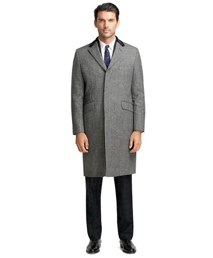 Man wears well-fitted gray Chesterfield overcoat, a pillar component of his custom capsule wardrobe