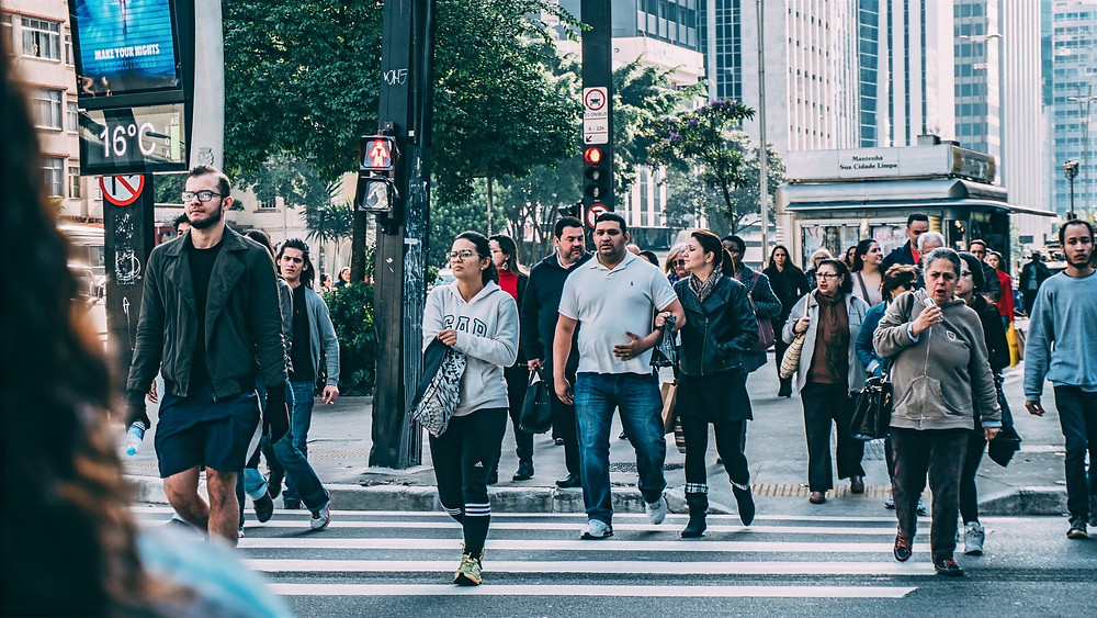 A group of pedestrians cross the street in a crowded metropolitan area.