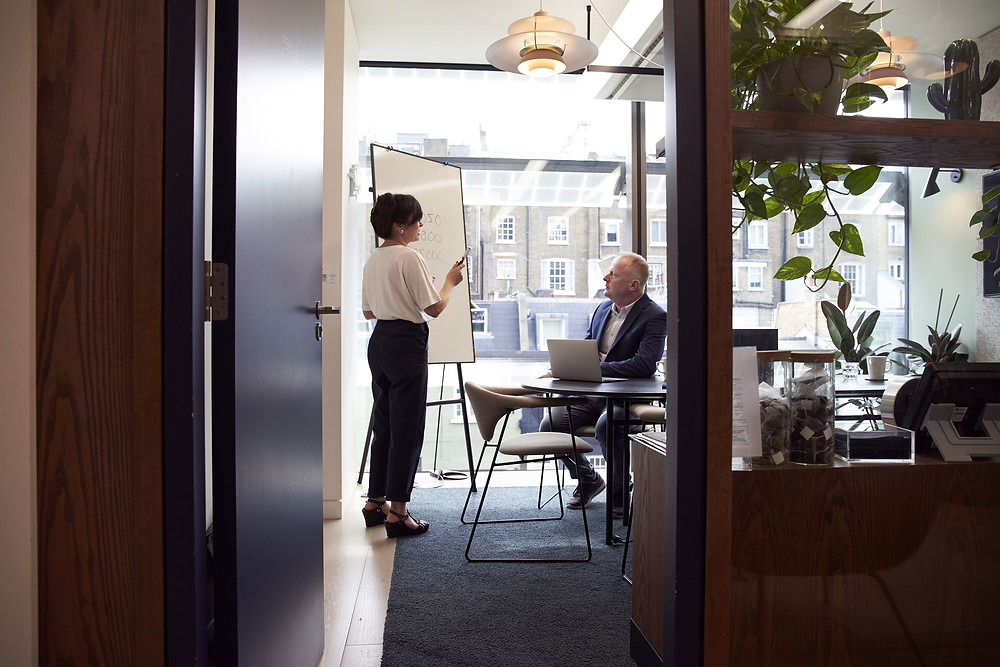 A strategy meeting is in session within an aesthetically designed office with office plants and large bright windows, as a woman holds a marker and communicates next to a whiteboard, while a man sits at a desk and listens.