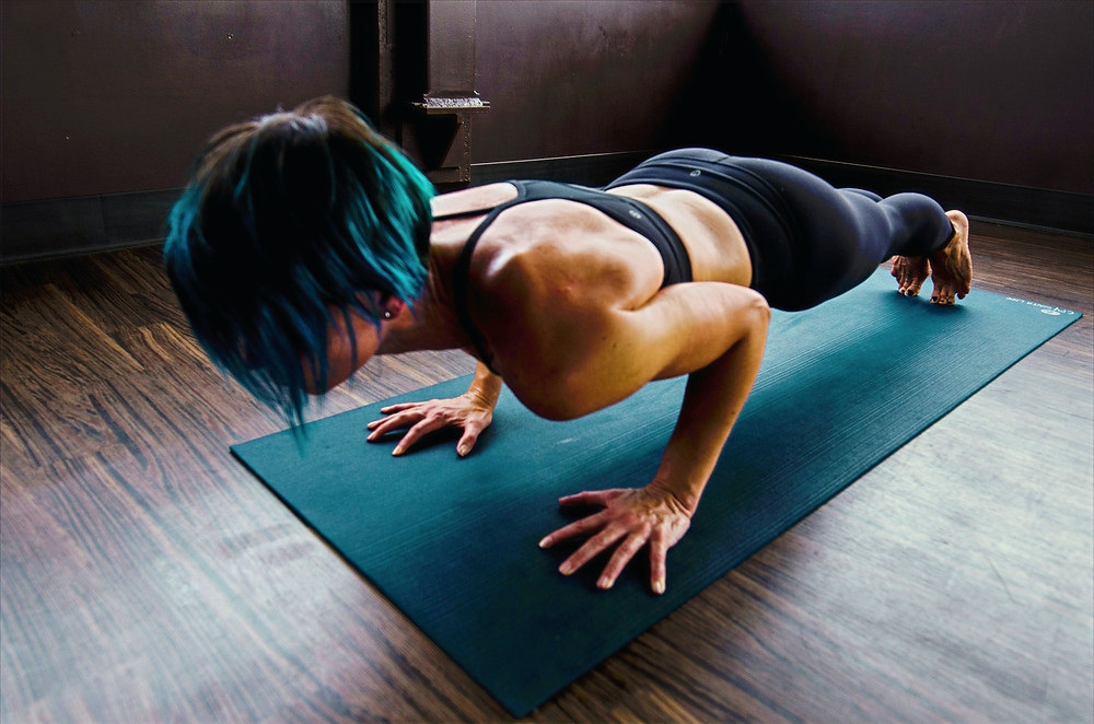A woman wearing an athleisure outfit of yoga pants and a sports bra focuses and holds a plank position on a yoga mat.