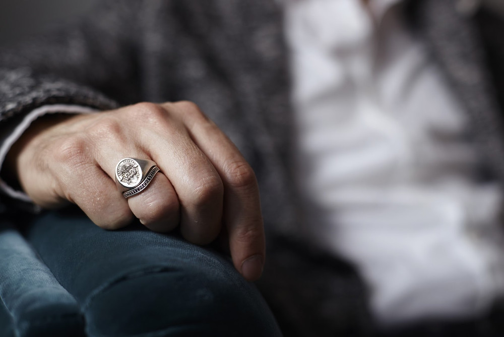 Man shows signet ring on his right ring finger, an elegant accessory for his capsule wardrobe, his arm resting on an armchair