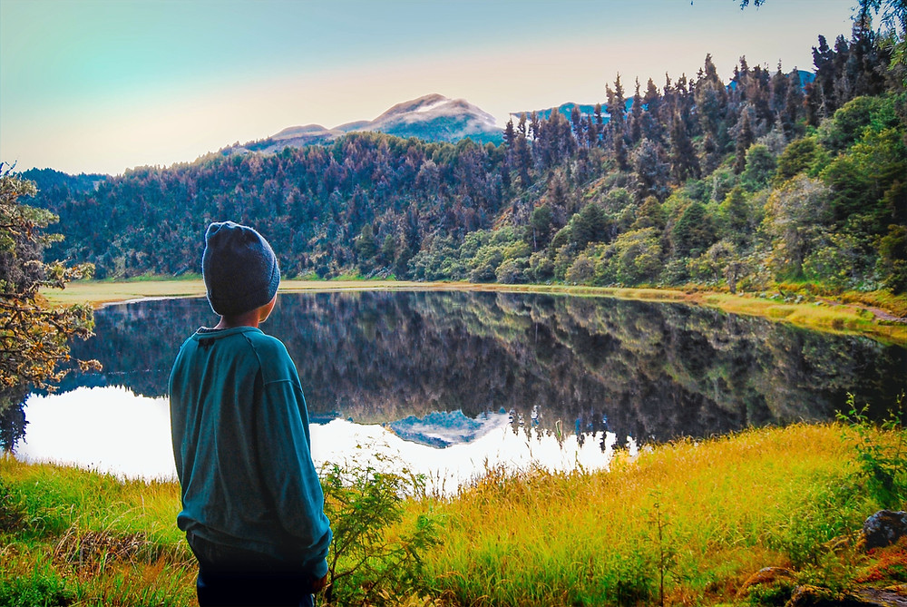 A child wearing a beanie and long-sleeved sweater gazes out across a lake and mountain landscape.