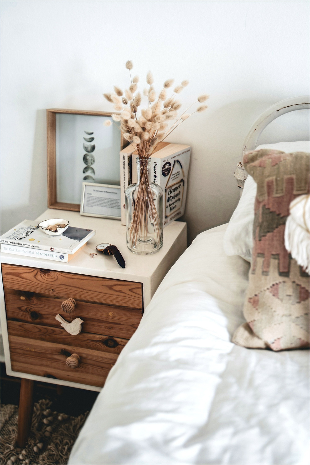 An arrangement of boho style decorations are photographed on a nightstand beside a bed.