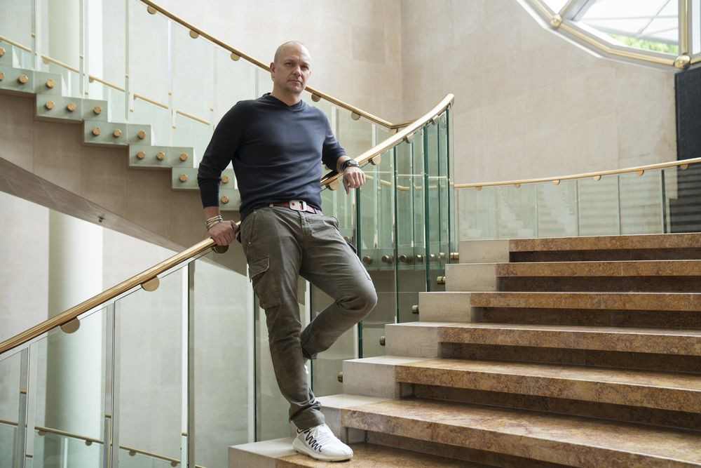 Tony Fadell poses for a photo on an ornate staircase while leaning against a golden railway fitted with glass panels.