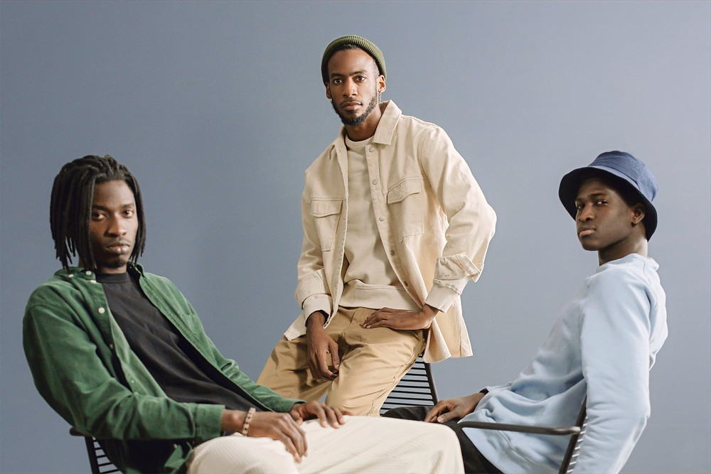 Three men sit on wireframe chairs as they face the camera, sporting minimalist outfits as they pose for a photo shoot.
