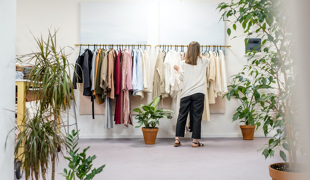 Woman standing in front of clothing rack situated at the back of a minimalist white room, surrounded by decorative potted house plants