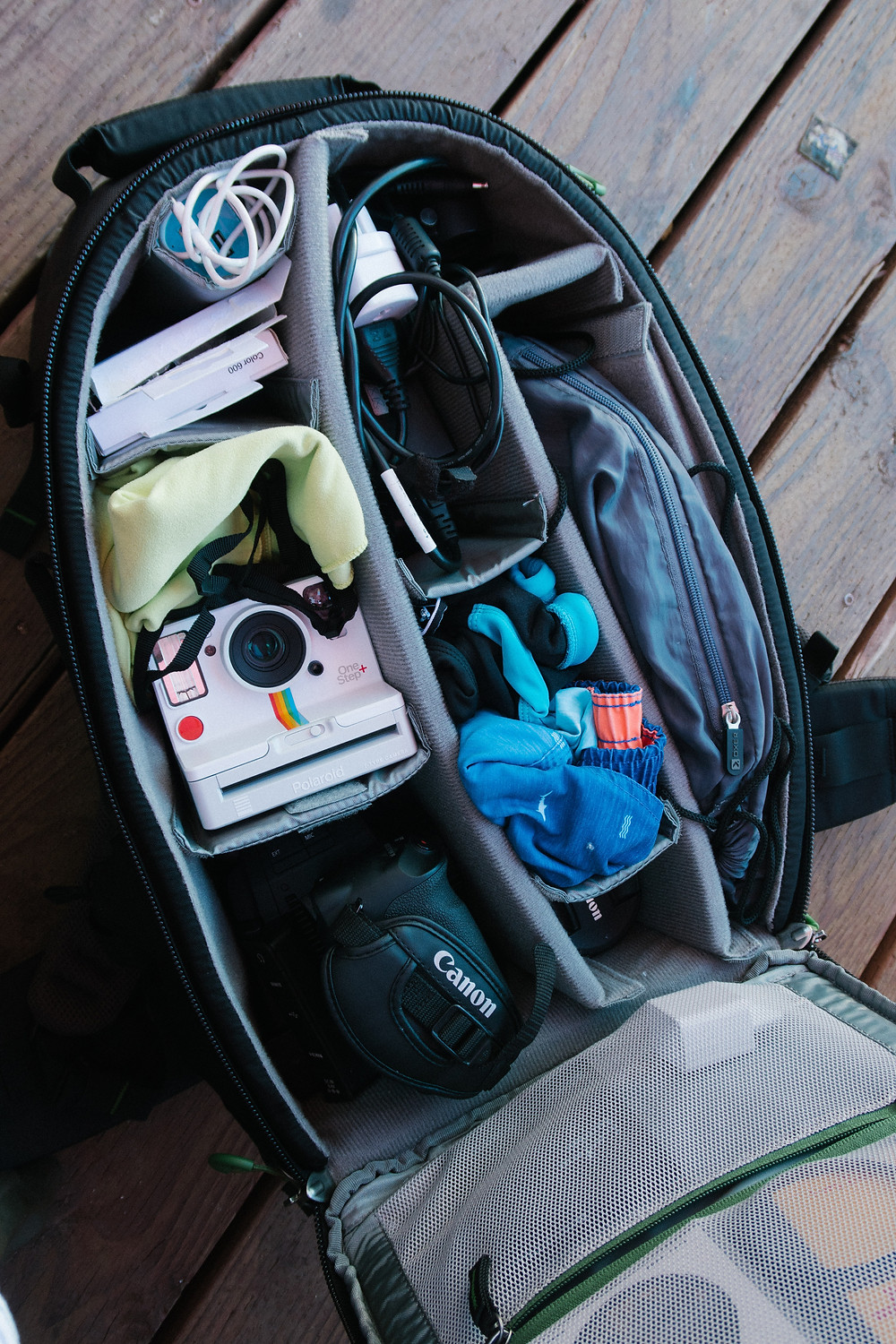 A bag is packed in a modular and organized manner, displaying contents including a campera, swimsuit, pack, electronics, and envelopes.