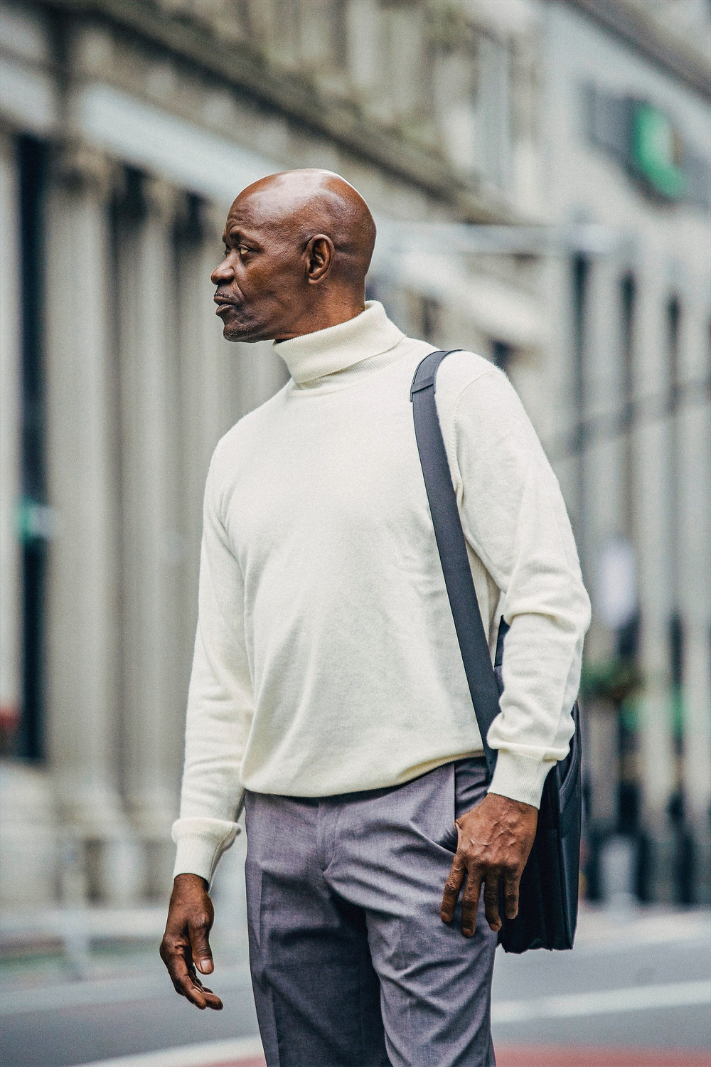 Well-dressed man sports a white knit turtleneck and hand bag draped over his left shoulder, while looking across the street in a metropolitan city.