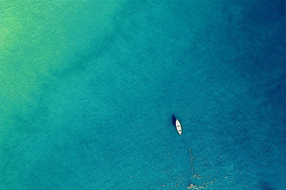 An aerial photograph shows a boat resting on a calm, shallow ocean with multiple shades of blue and green colors.