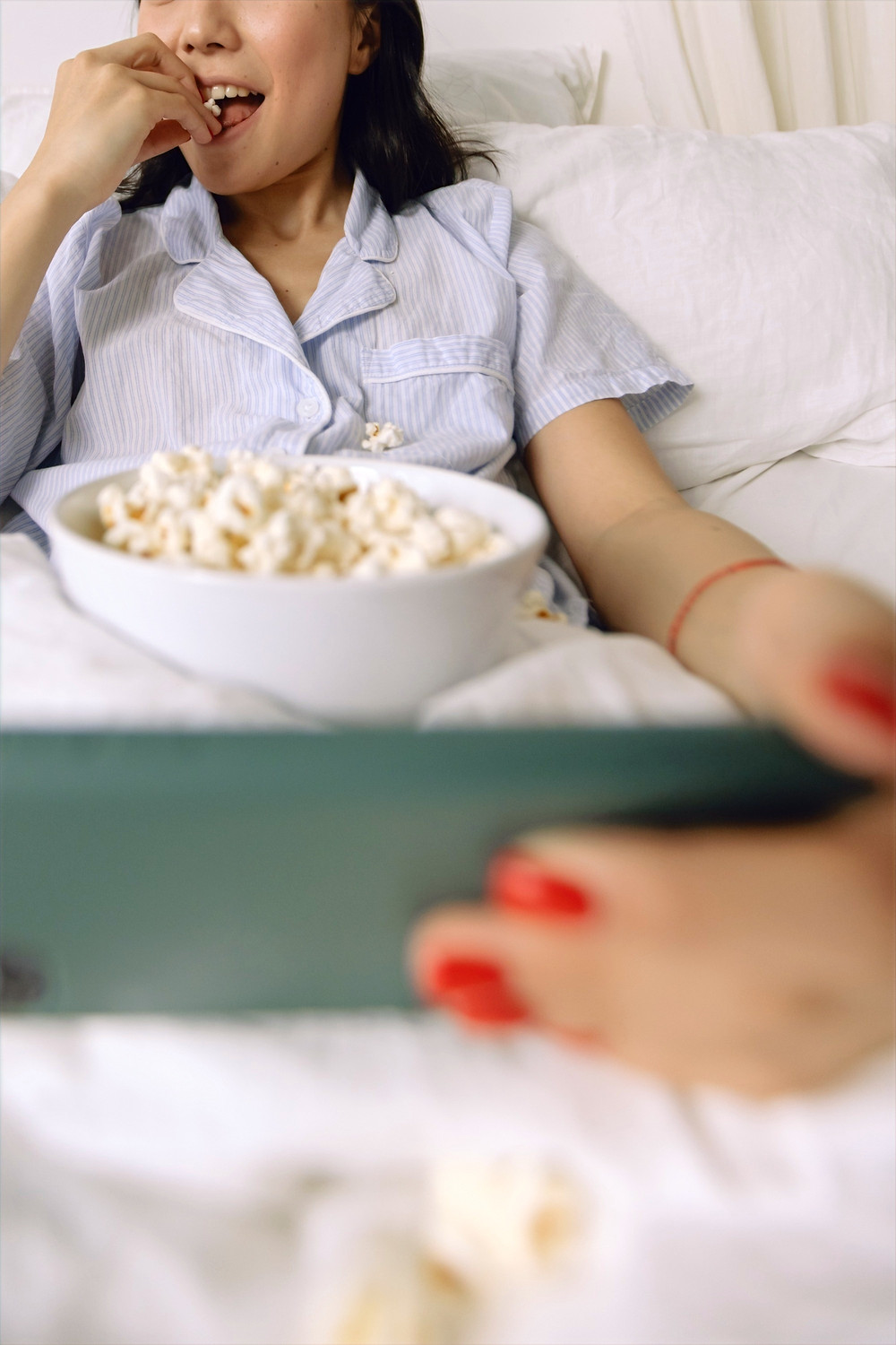 A woman wearing seersucker style pajamas holds a white bowl of popcorn delightedly raises a piece of popcorn to her mouth while capturing a photo on an iPhone.