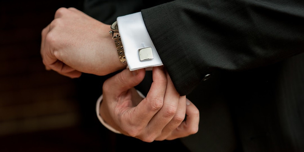 Man puts on square metal cufflinks as a final touch to accessorize his black jacket, a part of his custom capsule wardrobe