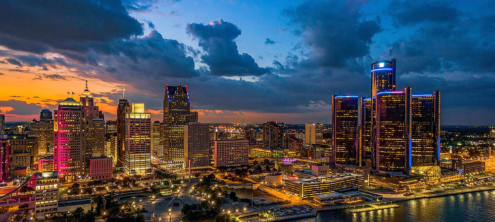 Aerial view of Detroit's downtown skyscrapers, illuminated in a multicolor rainbow, standing up against a clouded sunset backdrop that is orange and blue.