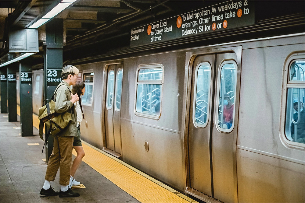 Two people begin to take steps towards a subway train before the doors open.