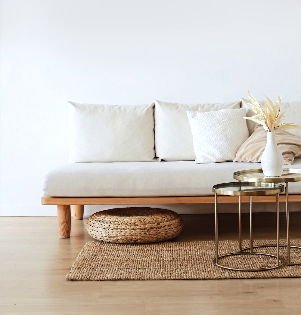 Minimalist-inspired room with a white couch and wooden table, a style that can be incorporated into a capsule wardrobe
