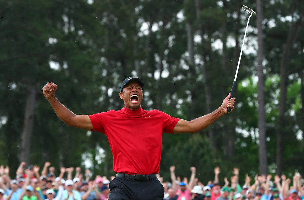 Tiger Woods celebrates while wearing a red Nike turtleneck on the golf course at The Master's, a core component of his custom capsule wardrobe