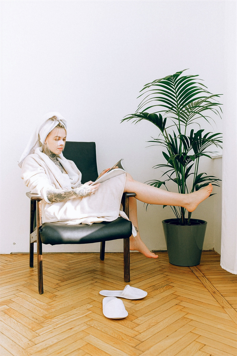A person wearing a hydrating sheet mask and robe reclines on an armchair in a minimalist room while reading a magazine..