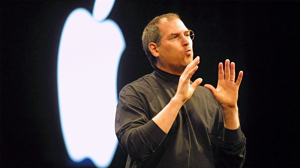 Steve Jobs stands in front of a bright Apple light fixture and wears a black turtleneck while speaking emphatically and using hand gestures.