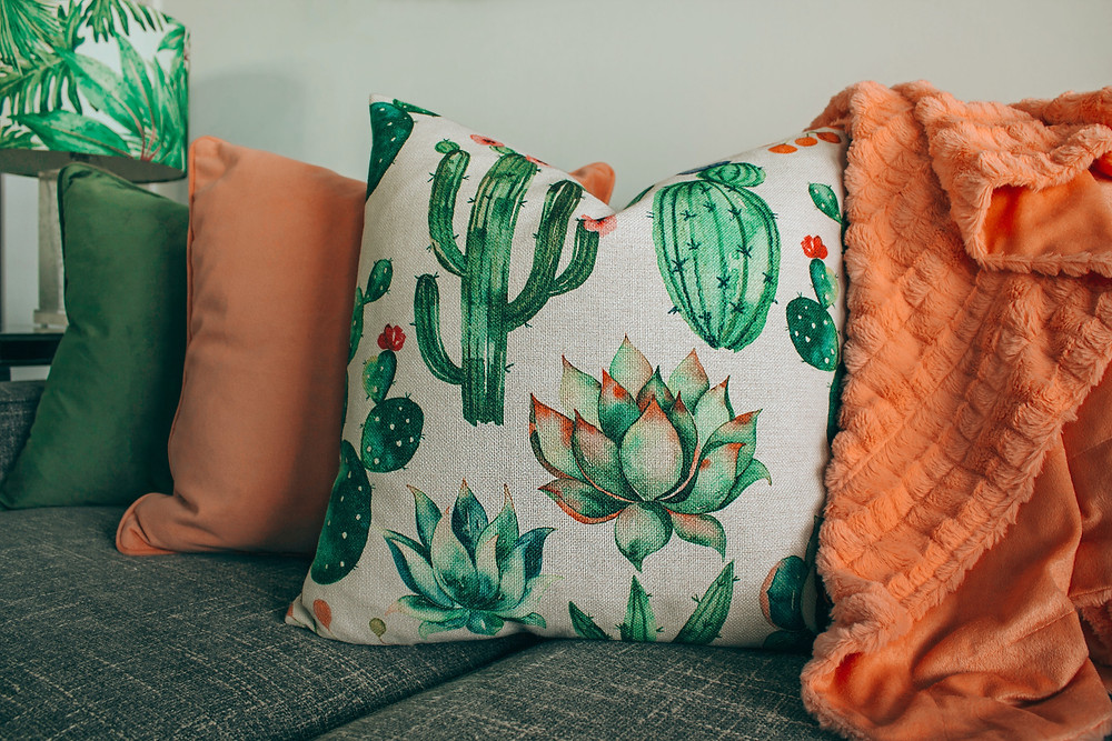 A cactus printed boho pillow arranged in a line with an assorted set of orange and green pillows.