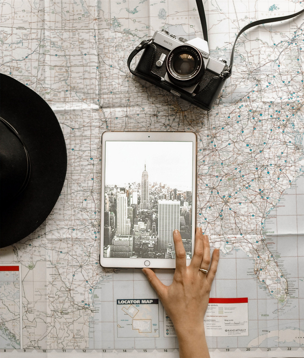 A hat, camera, iPad, and map are laid out on a table as a hand points on the touch screen to organize a travel plan.