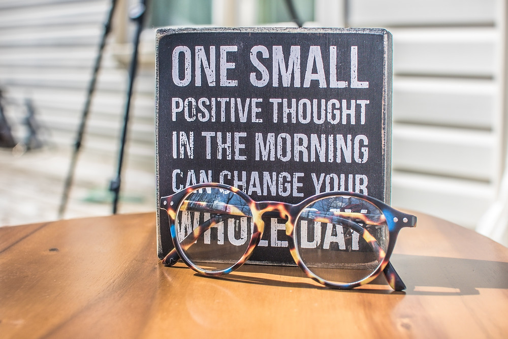 """A photograph of a pair of glasses on a table, in front of a sign printed with the words """"one small positive thought in the morning can change your whole day."""""""