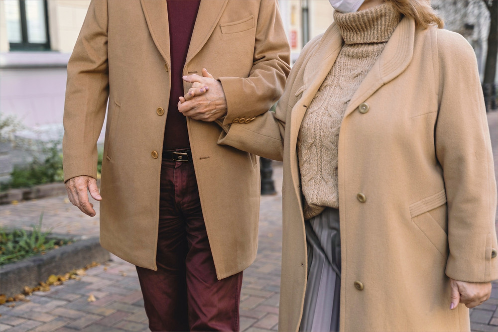 Couple with matching cashmere overcoats hold hands in a relaxed manner while walking on a clean sidewalk.
