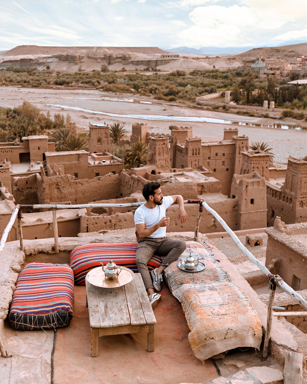 A man sits on a stone terrace in a desert location, wearing a minimal t-shirt and pair of paints while having tea..