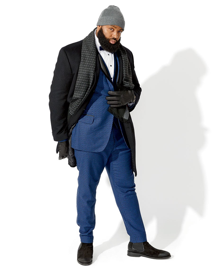 Akiem Hicks of the Chicago Bears wears a wool knit beanie, a patterned scarf, and thick gloves to accessorize his suit