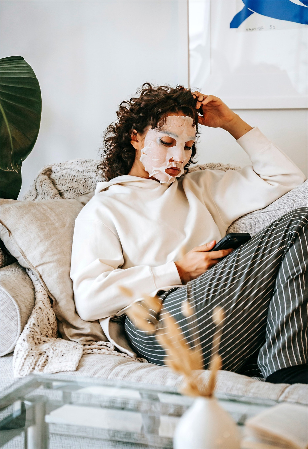 A person wearing a hydrating sheet mask checks their phone while lounging on a couch.
