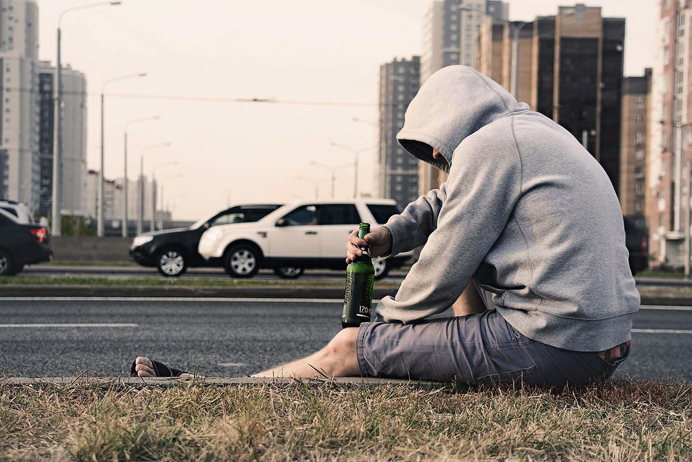 A man wearing a hood and shorts sits on the curb on the side of the road and holds a glass bottle of beer as traffic passes.