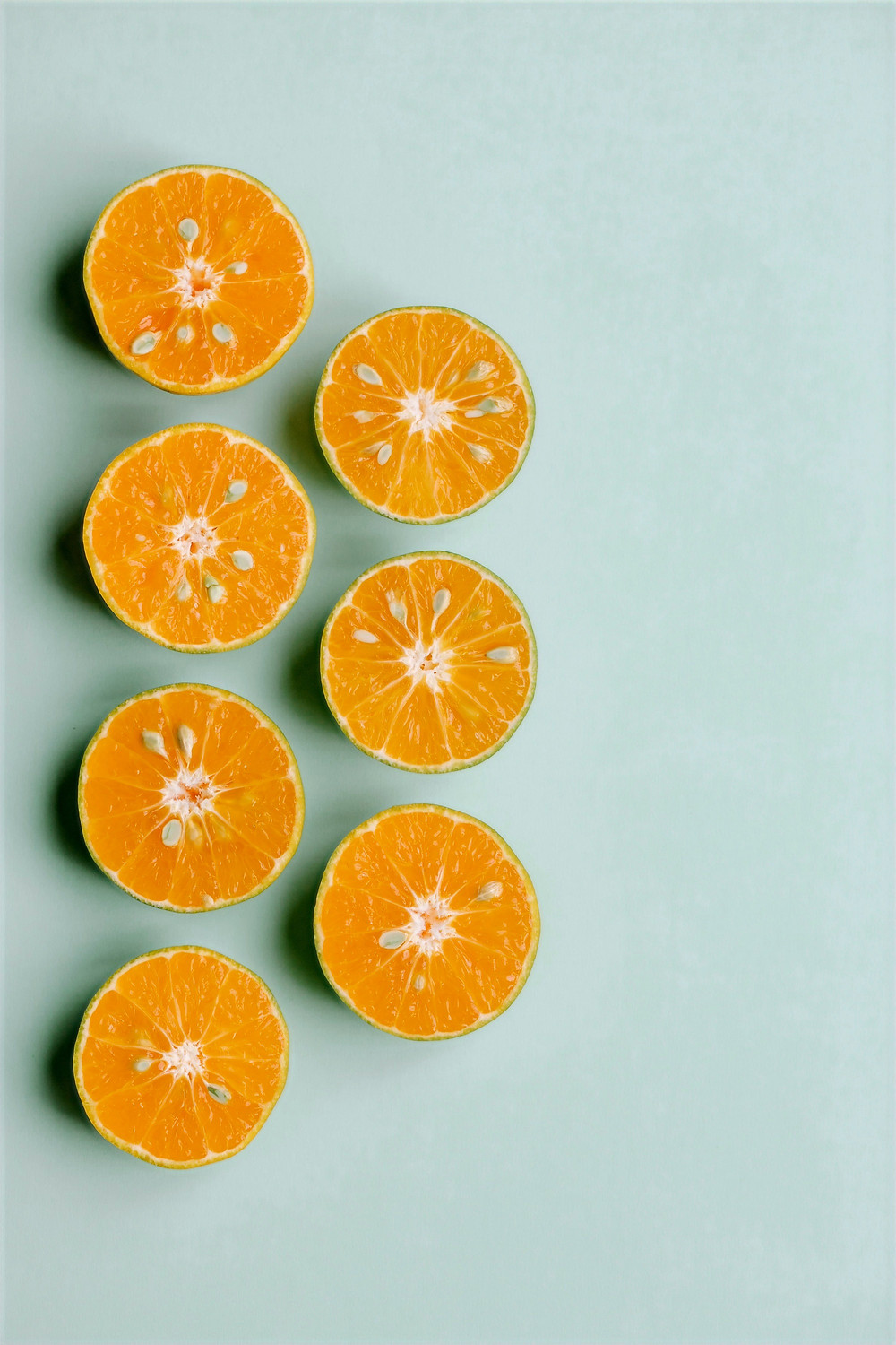Seven orange halves arranged neatly for a photo shoot.